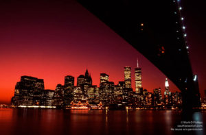 The Twin Towers of the World Trade Center beneath the Brooklyn Bridge roadway with blazing red sunset. Printed on  Silky Gloss paper