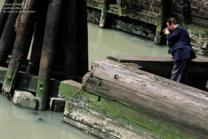 An NYPD Detective photographs a dead body floating in the Gowanus Canal in Brooklyn, NY at the Carroll Street Bridge.