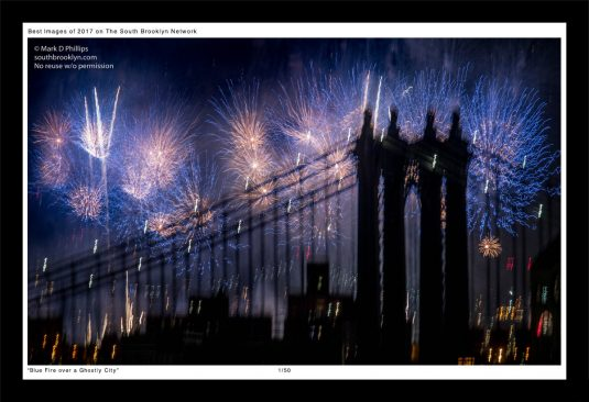 The 2017 Macy's Fireworks make a blue sky over the ghostly figure of the Manhattan Bridge in New York City. ©Mark D Phillips