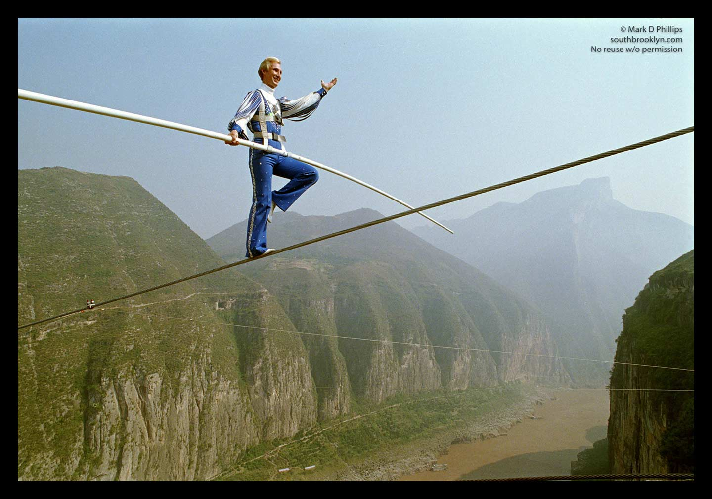 "Framed image of Jay Cochrane, ""The Prince of the Air"", completes The Great China Skywalk over the Yangtze River in Qutang Gorge, China, on October 28, 1995. The skywalk was and is the greatest ever made spanning half a mile between the canyon walls and 1,350 feet above the river. ©Mark D Phillips"